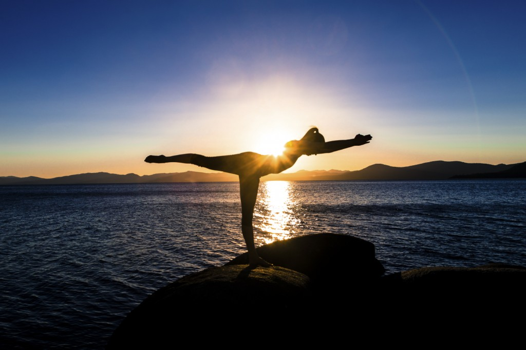Young woman balancing on one leg at sunset
