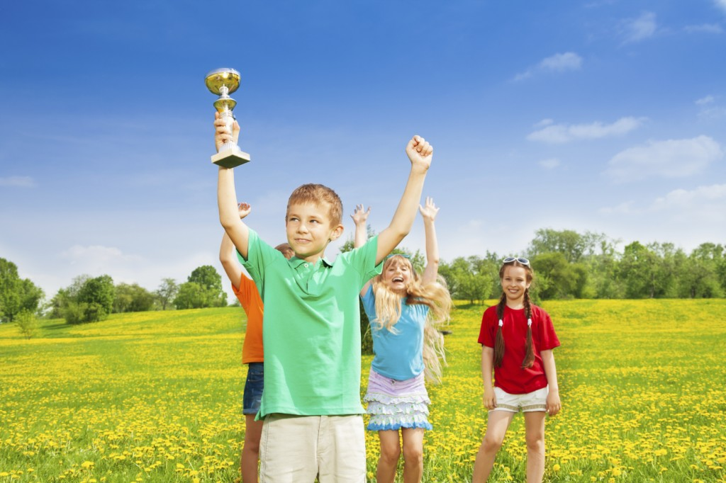 Portrait of happy little boy holding prize in lifted hands cup with his team cheering on background