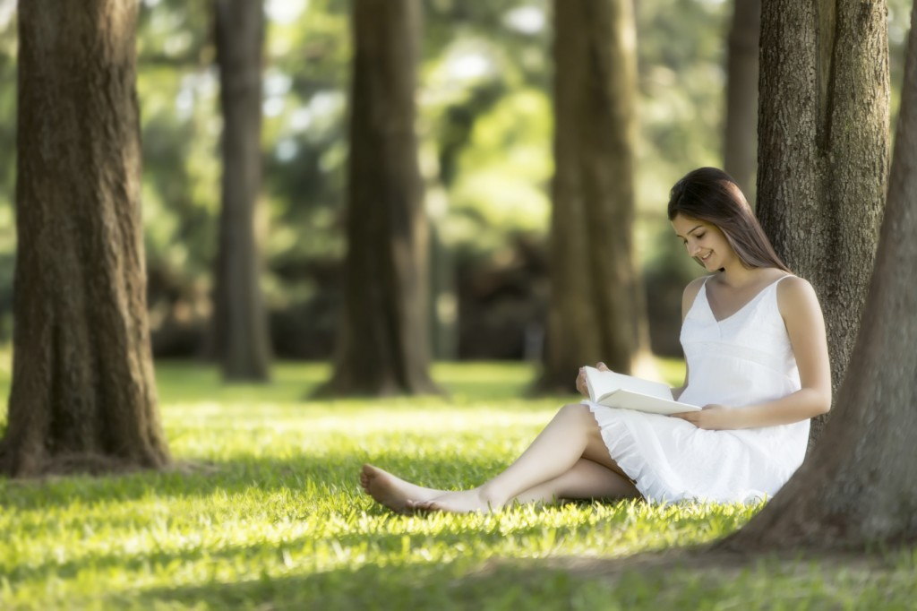 Relaxed, young woman reading book on green grass
