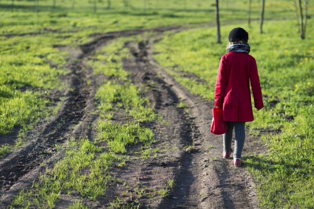 girl in red coat going far away by dirty country road,