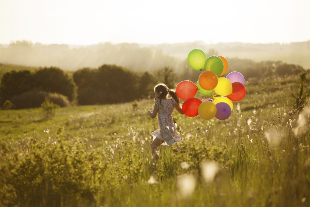 Happy little girl running across the field