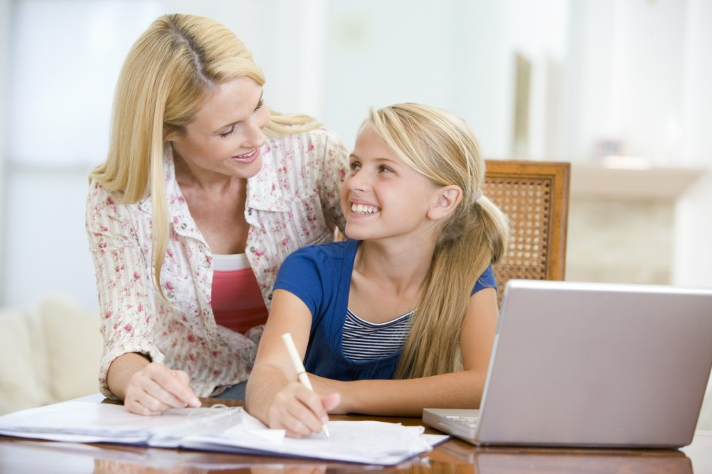 Woman helping young girl with laptop do homework in dining room