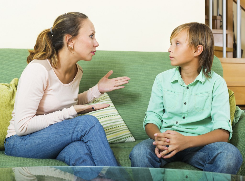 Serious middle-aged mother and teen boy talking in home interior