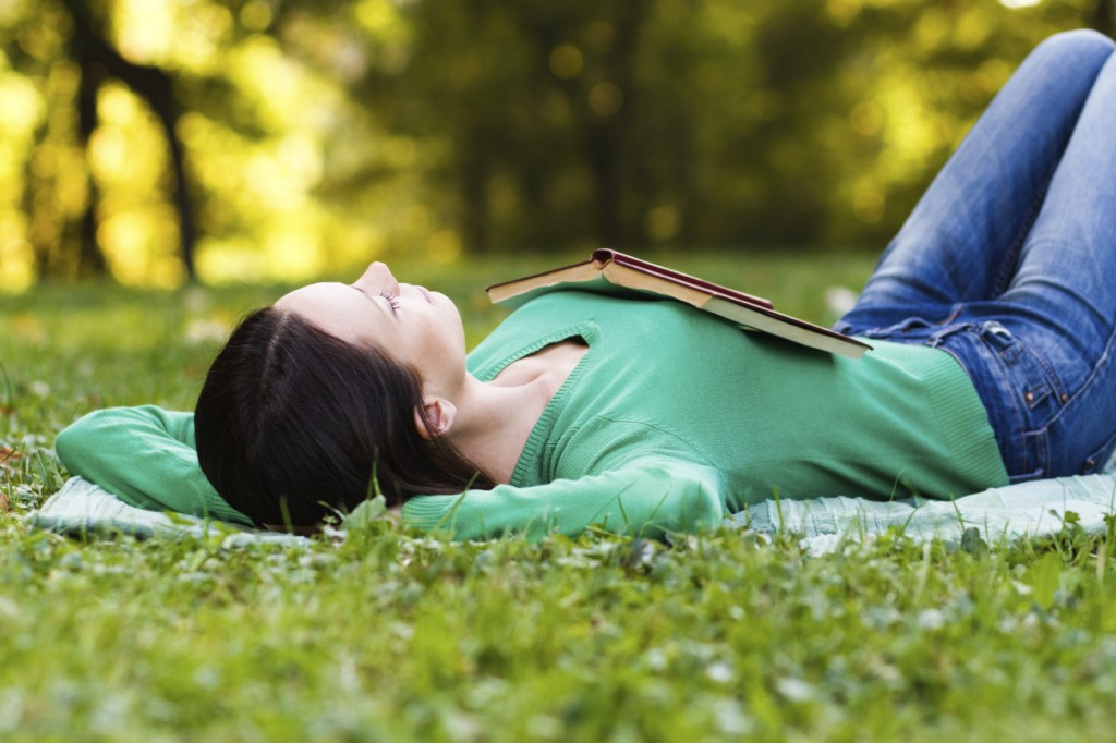 Young woman lying down on a field and sleeping.