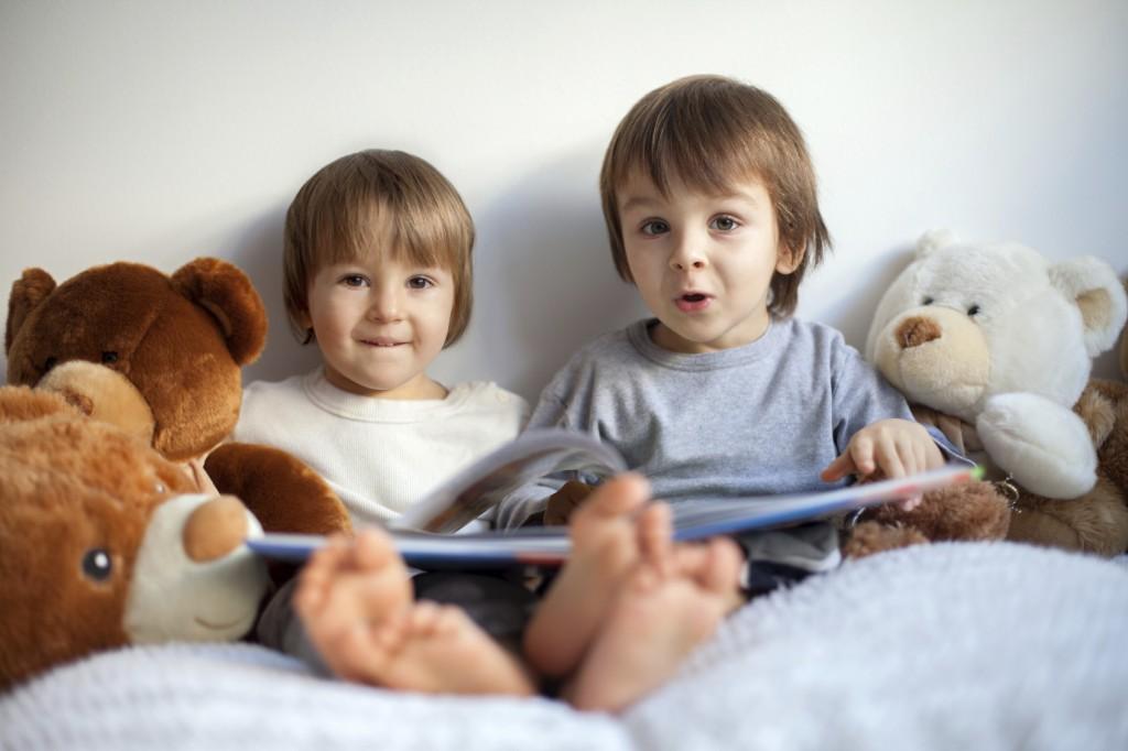 two little boys, reading a book, having fun