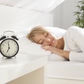 beautiful girl sleeping in her bed. focus on clock