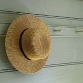 Straw hat hanging on a peg