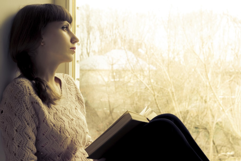 Young woman reading book near the window.