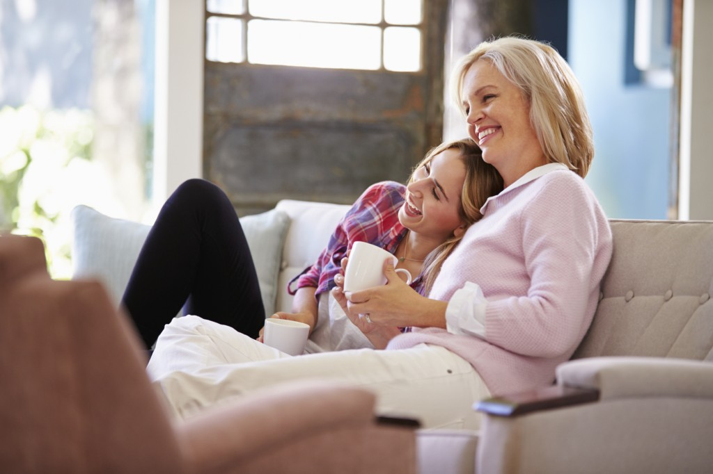 Mature Mother With Adult Daughter Watching TV At Home
