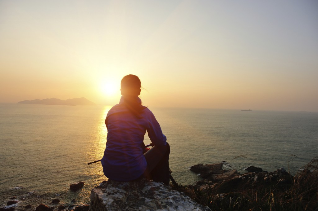 woman hiker sit on rock face the sunrise
