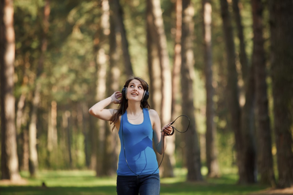 Girl walking in a park and listening music