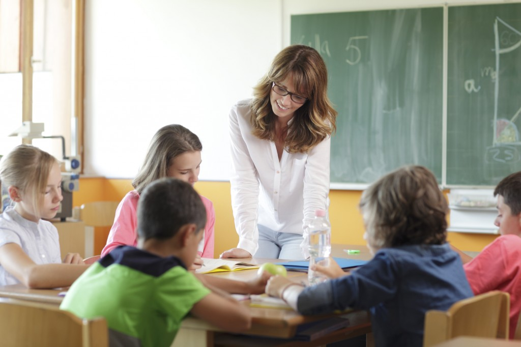 Elementary classroom. Focus on teacher standing in front of chalkboard.