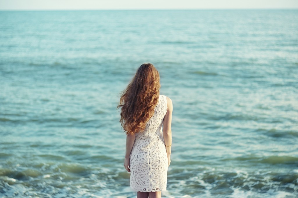 Beautiful woman with red hair at the sea