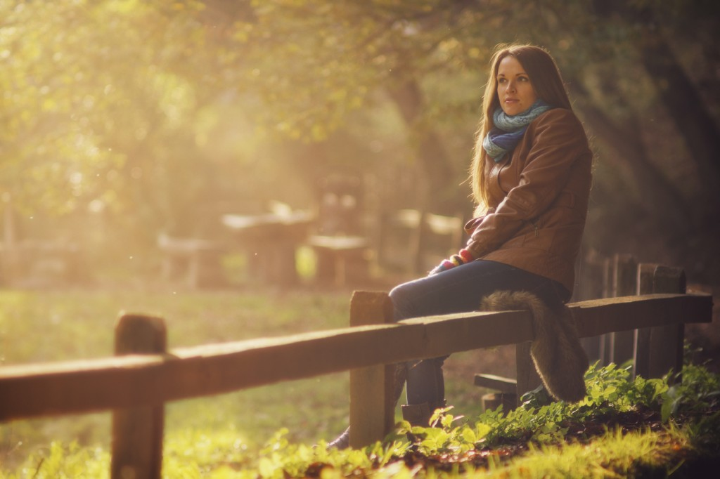 woman sitting on a fence in autumn