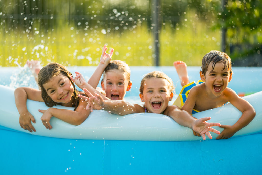 Siblings - four happy young kids in swimming pool