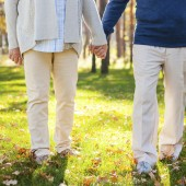 Spending great time in park. Close-up of senior couple holding hands while walking by park together