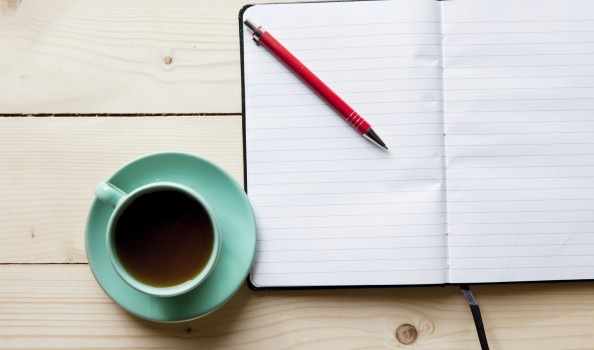 Open a blank white notebook, pen and cup of tea on the desk