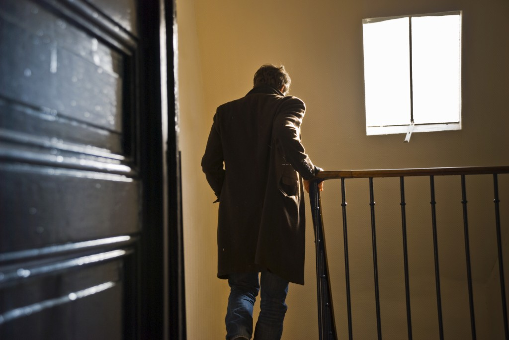 man walking out of room and down stairs