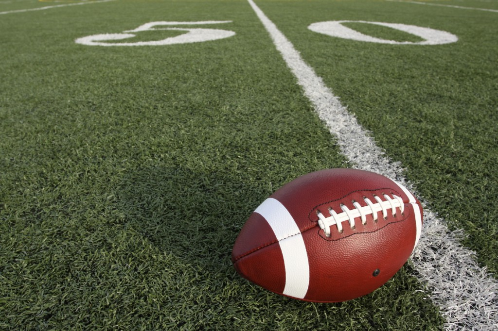 a football sitting on the 50 yard line.