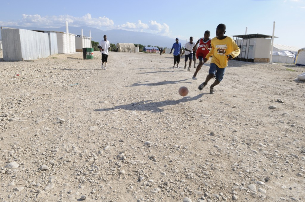 Haitian kids playing soccer outside.