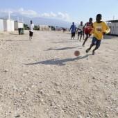 Haitian kids playing soccer outside.