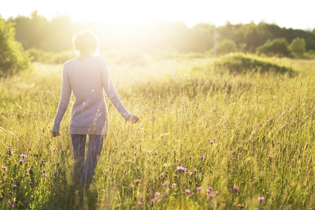 Woman walking without fear through a sunlight field