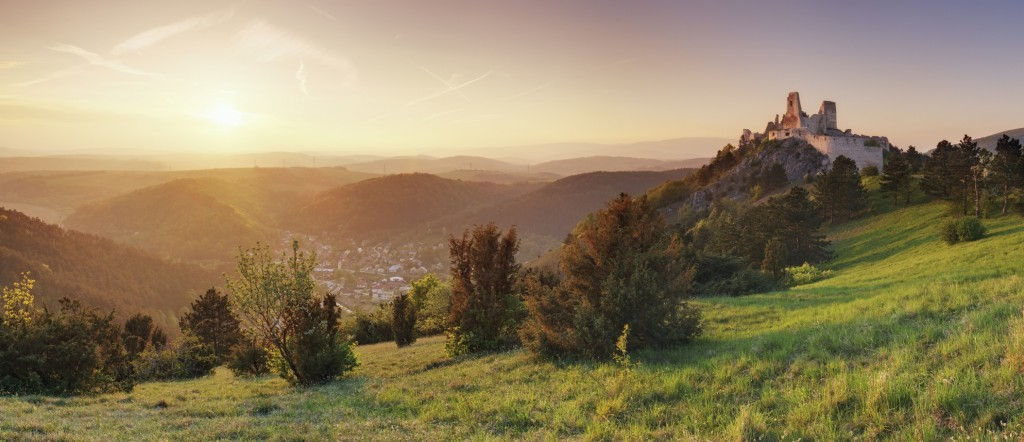 Sun setting over a hilly landscape and a distant castle.