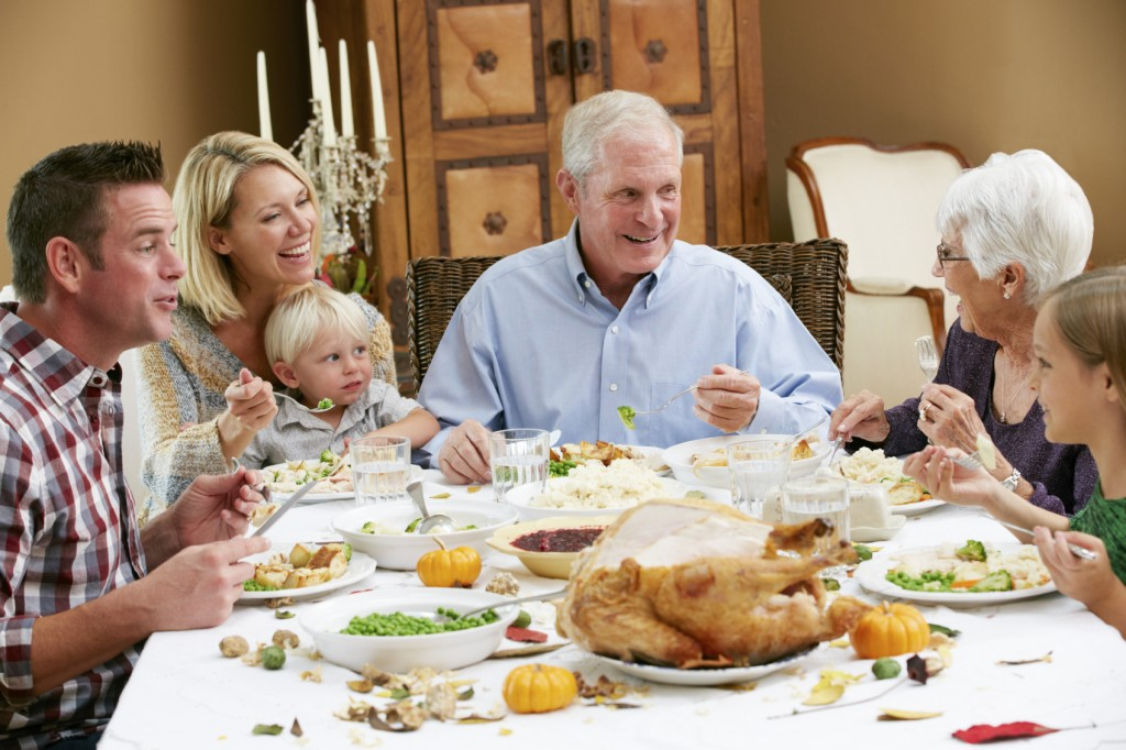 Multi Generation Family Celebrating Thanksgiving Eating Food At Table Smiling