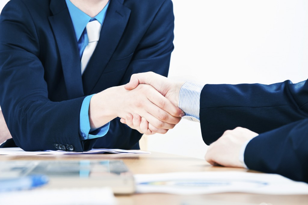 Two businessman shake hands above conference room table