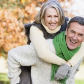 Senior man giving his wife a piggyback ride through autumn woods