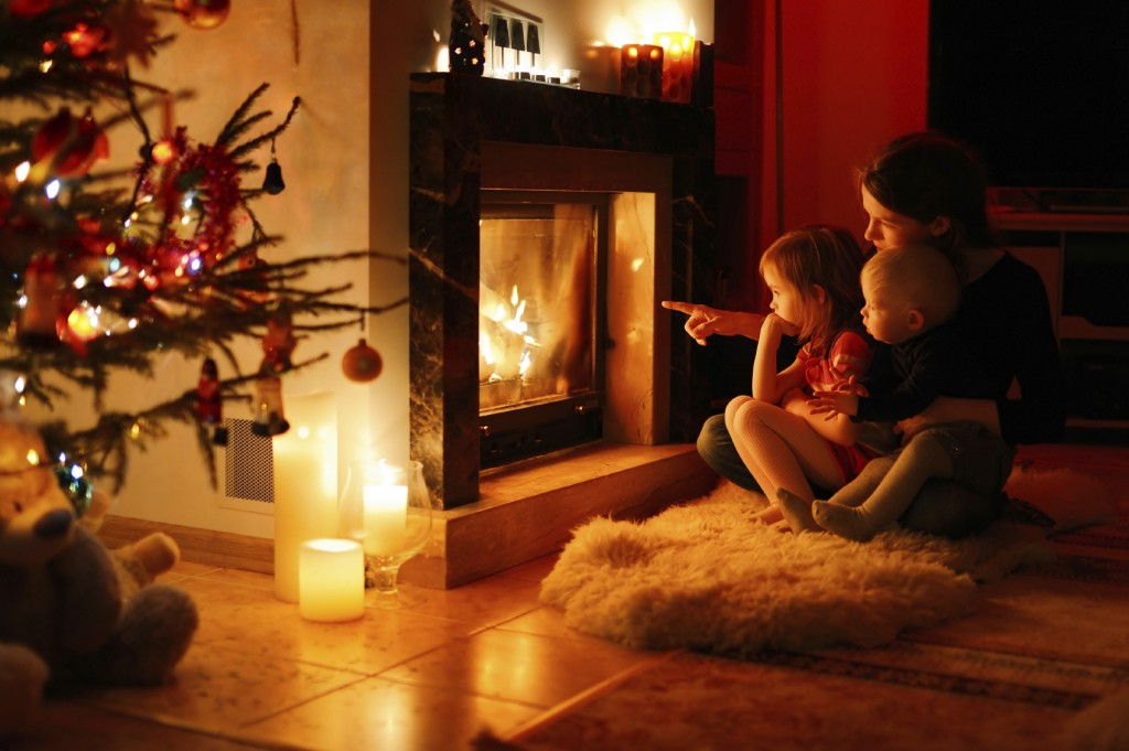 Young mother and her daughters by a fireplace on Christmas