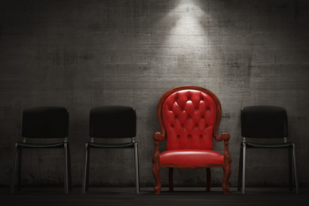 Red wing back chair among standard modern chairs.
