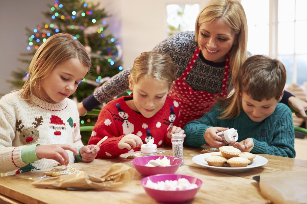 Mother And Children Decorating Christmas Cookies Together.