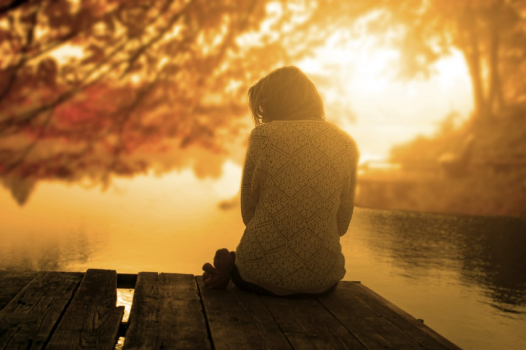 woman sitting on a dock watching the sun set in fall.