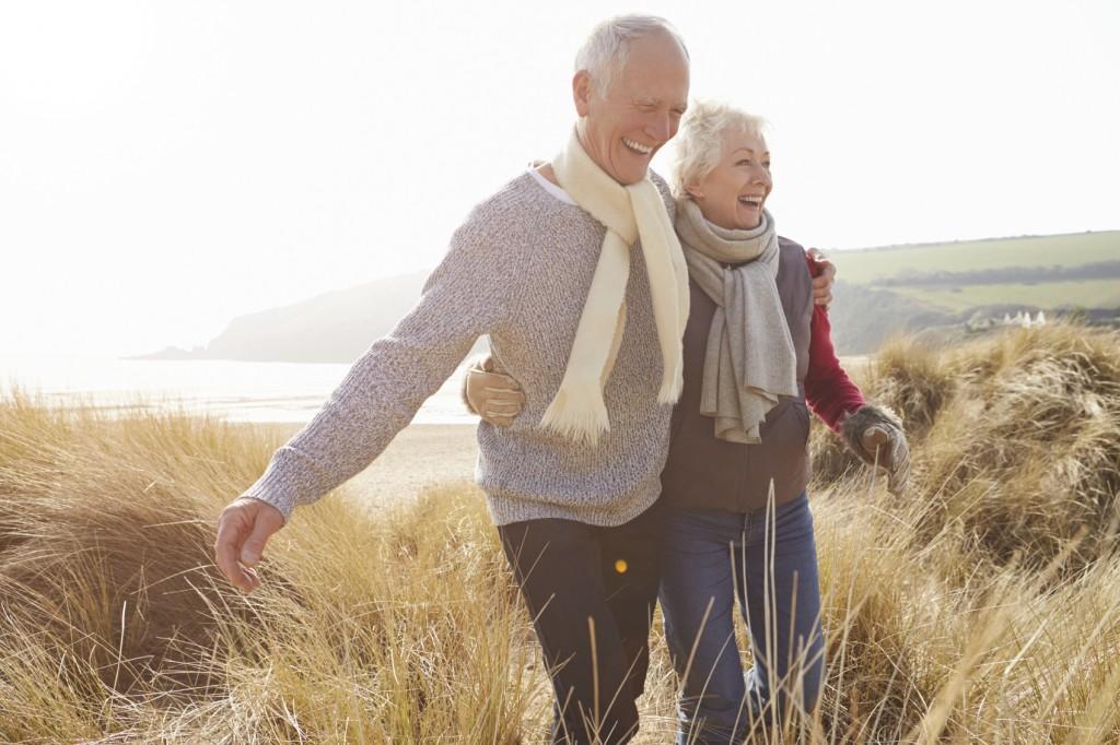 an senior couple walking through sand dunes in late fall