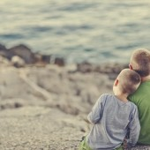 two young boys sitting on the rocks
