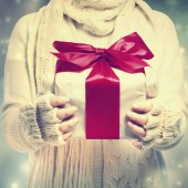 Gift box with red ribbon in the snowing night