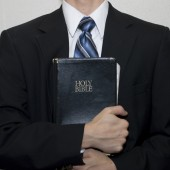 man in suit holding a Bible.