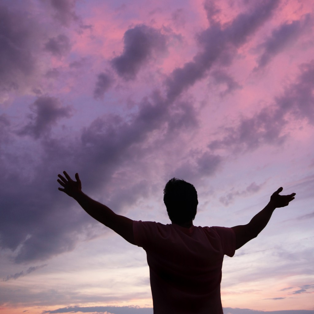 man with arms raised, Pink sunset in the background