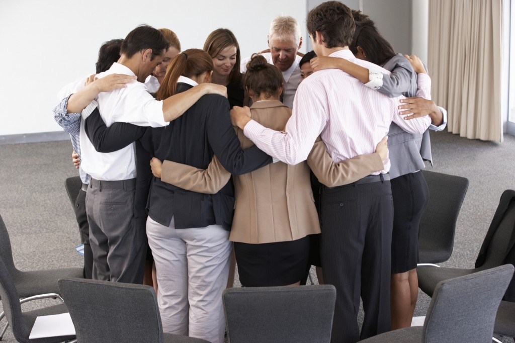 group of people praying in a circle.
