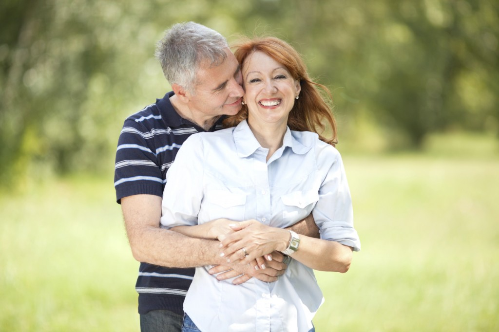 Portrait of happy mature couple smiling and walking in park.