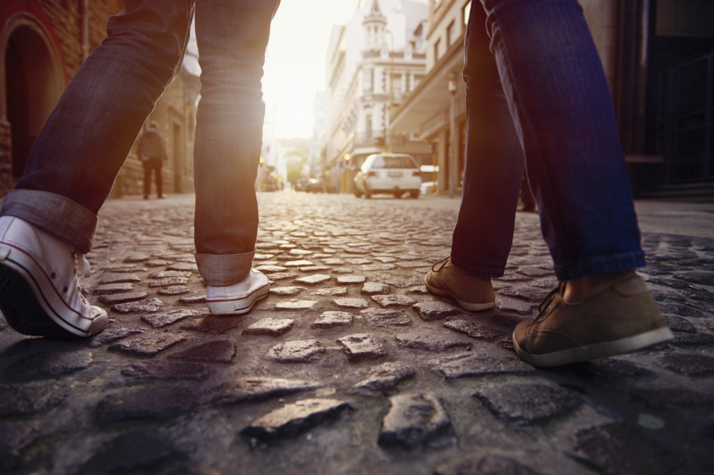 couple walking on cobblestone street