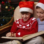 siblings in Santa caps reading book together on Christmas evening