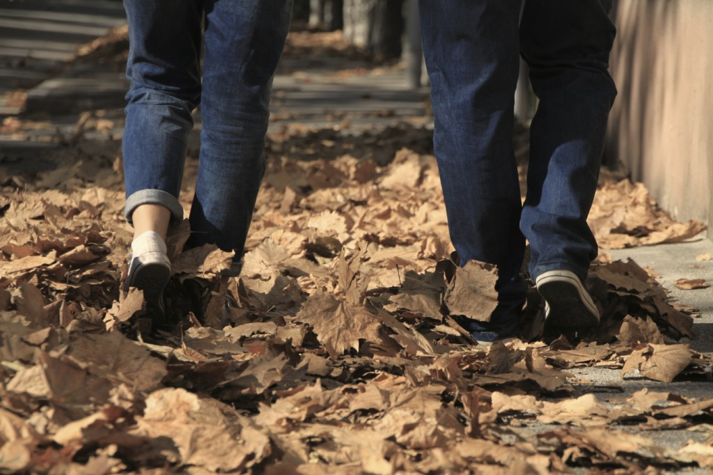 Young couple walking on the path full of leaves