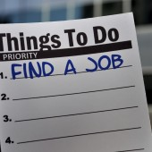 A to do list with the words, 'FIND A JOB' written as the number one priority is held in front of an office building.