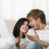 Happy couple reading a letter in their living room