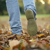 Male walking with boots on autumn leaves