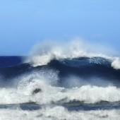 Wave crests and rolls toward shore