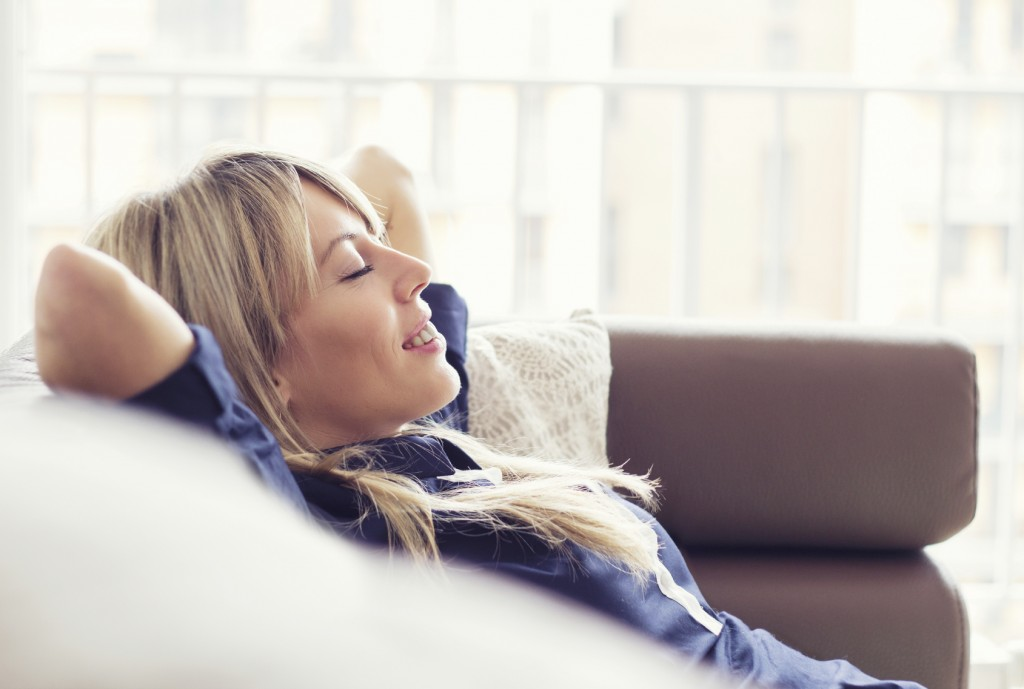 Relaxed young woman lying on couch.