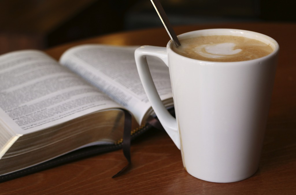 Bible opened to Luke with a cafe latte in a Coffee House.